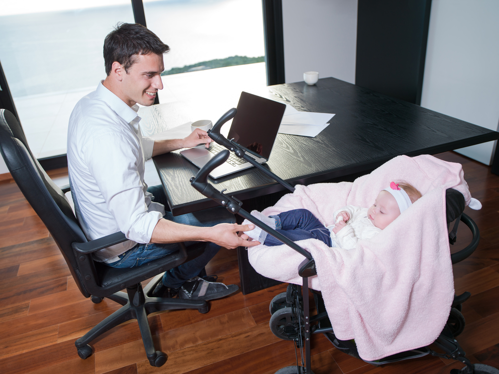 young man parent working on laptop computer at home office and take care of baby